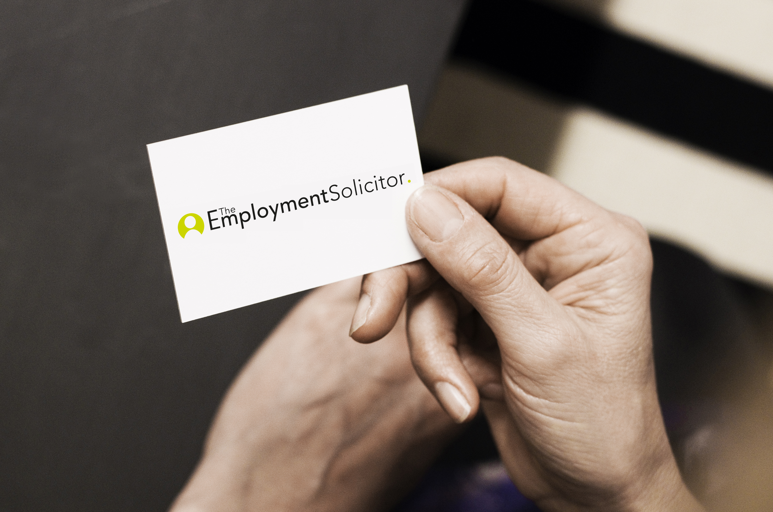 a female hand holding an Employment Solicitor business card