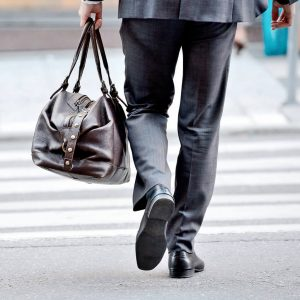 A man walking away from his job a bag in his hands